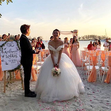 A bride stands on a white sand beach facing the camera in a fluffy bridal gown, holding her white bouquet down toward the ground with both hands, preparing to toss it over her head into a crowd of bridesmaids in light pink dresses.