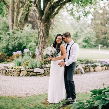 A bride and groom stand happily under a large tree with rocks surrounding it. The bride has long black hair and holds a bouquet of small white blooms in front of her belly.