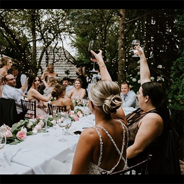 A bride sits with her wedding party at white tables in front of a forest background with fairy lights and they all raise their respective glasses into the air.