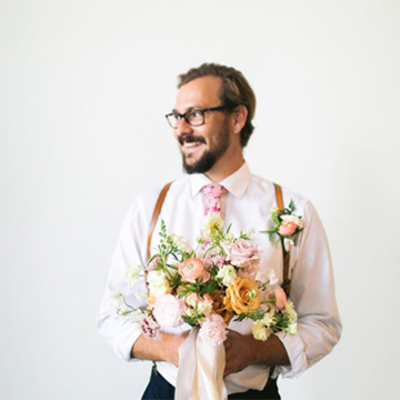 A man with black glasses on turns his head to the side and smiles while wearing a pink tie and suspenders and holding a bouquet with a peach ribbon handle, yellow garden roses, light pink roses, peach and white ranunculus, and various greenery.