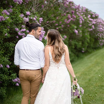 A bride and groom walk next to a wall of purple lilacs. The bride holds a bouquet of matching lilacs with white ribbons  at her side.