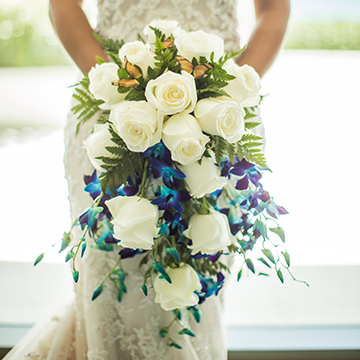 A bride in a mermaid tail lace wedding gown holds a cascade-style bouquet of white roses and blue variegated vine blooms.