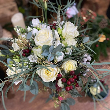 A bouquet of white roses, red berries, white berries, and messy sage greenery is held above a wood table background.