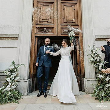 A bride and groom are happily emerging from a building while the bride hodls her small bouquet up above her head in celebration.