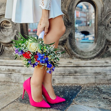 A woman in pink pointed heels holds a colorful bouquet of roses, baby's breath, and various blue and red flowers near her calves while standing in front of an old concrete bridge or structure of some sort.