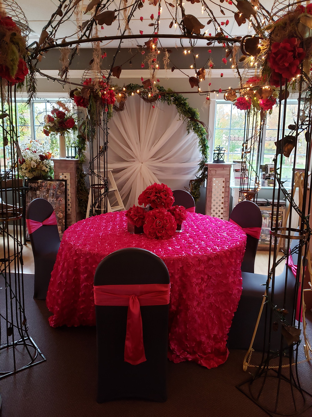 A bright pink table and chairs with a pink set of wedding flowers in the center.