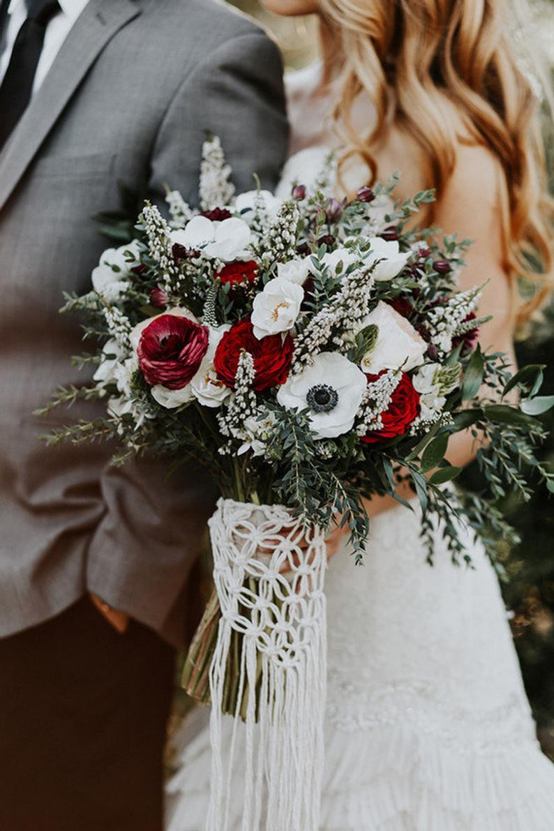 A bride holds a bouquet of white anemones, red roses, baby's breath, and greenery with a white macrame handle.