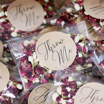 "A pile of clear plastic pouches with white and burgundy petals inside and labels that say, ""Throw Me."""
