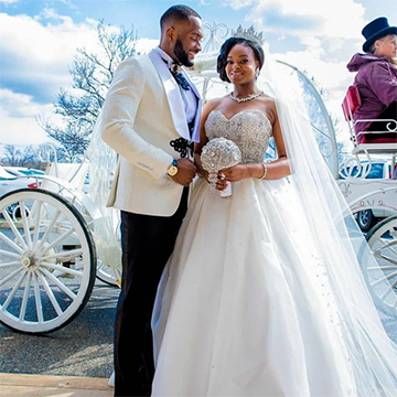 A bride and groom (both dressed in white) stand in front of a white horse-drawn carriage. The bride has a silver, sparkly crown on her head and holds a small round bouquet to match.
