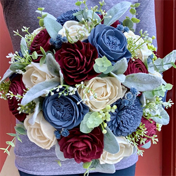 A woman in a light blue top holds a bouquet of burgundy roses, blue ranunculus, white roses, sage greenery, and various green textures in front of her belly.