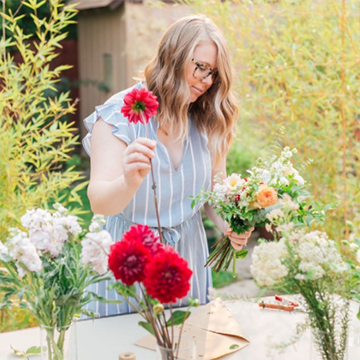 A woman with wavy blonde hair and black glasses is sorting flowers in various vases on a table with a bouquet she's creating in her other hand.