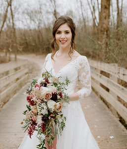 A brunette bride stands in her lacey wedding dress in front of a white bridge while holding a cascade bouquet of peach, red, and blue flowers.