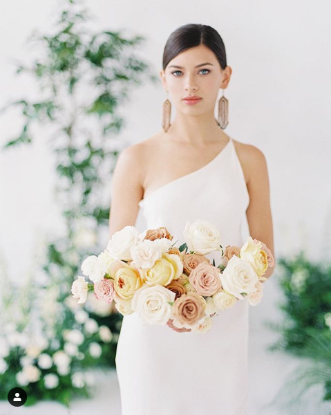 A young bride with tightly-pinned-back hair and large geometric earrings holds a bouquet of whites, tans, and light pinks in front of a plain, over-the-shoulder style wedding gown.