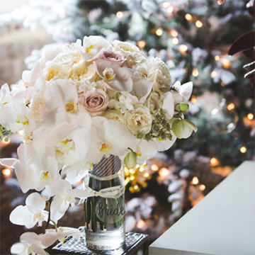 """A white bouquet of orchids, roses, and other light flowers in a glass vase that says """"Bride"""" in frosted letters sits in front of a snowy, lighted Christmas tree."""