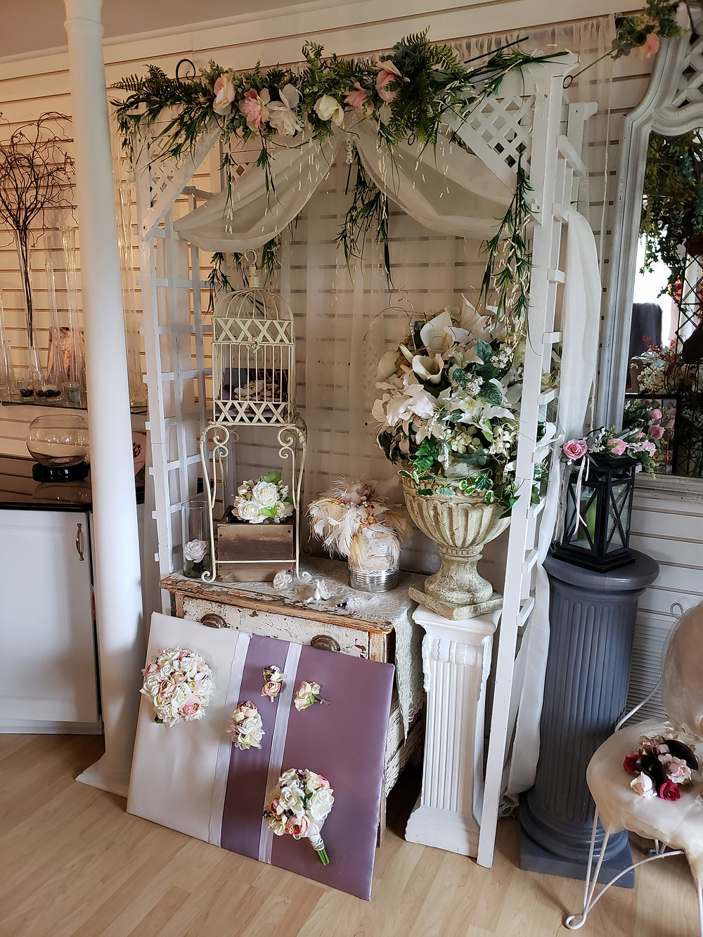 A white lattice arch with a display of white-based wedding flower bouquets.