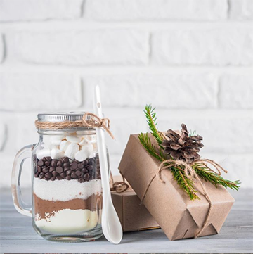 Two paper bundles sit in front of a white brick background with pine cones and evergreen sprigs tied on top. There's a jar with a handle that appears to have layers of dry ingredients, chocolate chips, and marshmallows and a white spoon.