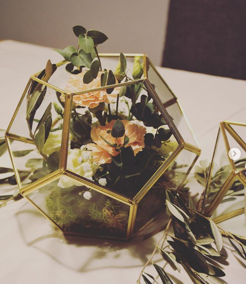 A small arrangement of flowers on a white table with a hexagonal cage of gold around them.