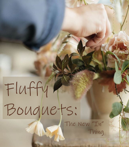 A bouquet with white and salmon-colored flowers and a fluffy accent reaching toward the camera.