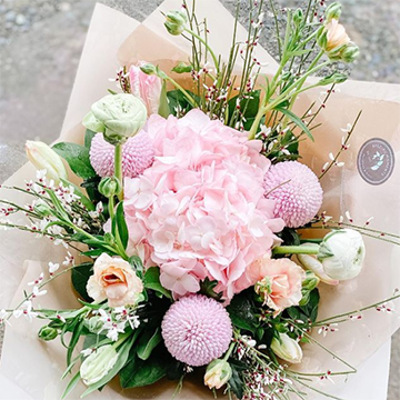 A box with light brown parchment paper holds a bouquet of light pink hydrangeas, light green buds, pink ball flowers, peach flowers, and various greenery.
