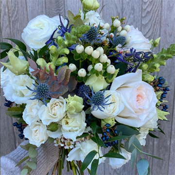 A sweatered arm holds a bouquet up in front of a light tan wooden background. The bouquet is a mixture of blue mountain thistle, blue privet berries, small white berries, sage greenery, and white roses of various sizes.