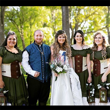 A bride holds her bouquet with her groom (in a blue medieval vest) and her bridesmaids (in green dresses with white and brown corsets, holding hooded lanterns) in the bright woods.