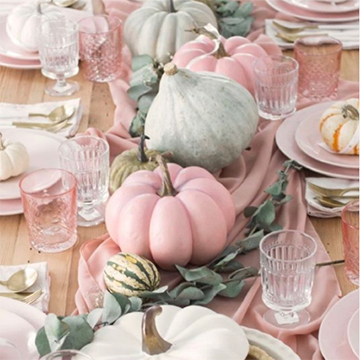 A close-up of an elegantly-set table of pink and silver cutlery with small pink and white pumpkins as decorations atop pink pieces of fabric.