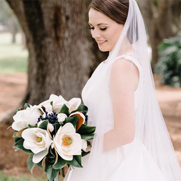 A brunette bride holds her bouquet in front of her and looks over her shoulder. Her bouquet is full of large, white magnolias and various foliage. She stands in front of a large tree.