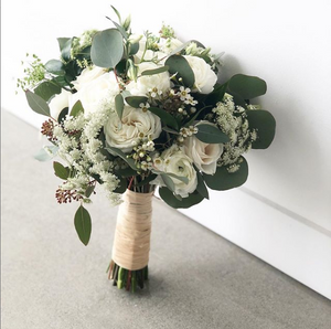 A hand-tied round bouquet with white roses, messy greens, and white baby's breath flowers leans against a white wall.