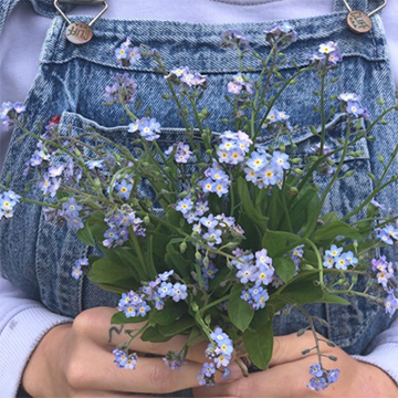 A woman in o=blue denim overalls holds a simple bouquet of messy light blue forget-me-nots in front of her chest.