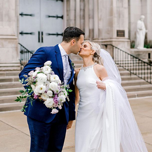 A bride and groom kiss in front of the church steps while the groom holds the bride's bouquet of white and purple flowers for her.