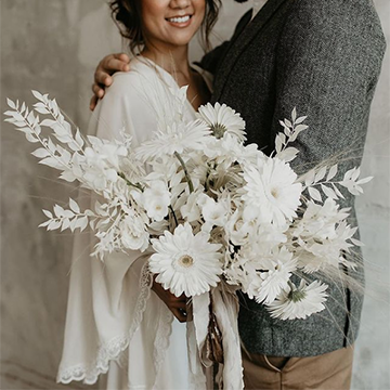 A couple hugs and hold a white bouquet of garden daisies, long leafy pieces, roses, and more in front of them.