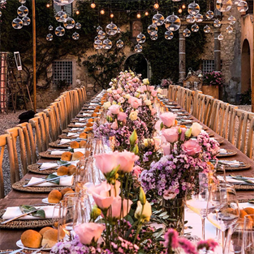 A wooden table sits with a dizzying array of pink roses, purple flowers, and yellow tulips that seem to go endlessly down a long table, glass bubbles hanging above beautifully in dawn sunlight.
