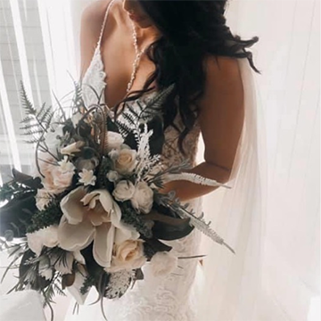 A bride holds a large bouquet of messy ferns, big white magnolias, and various smaller white flowers while standing in front of a sunny window.