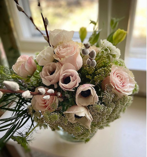 A bouquet of pink roses and anemone with greens and soft pussywillow accents.