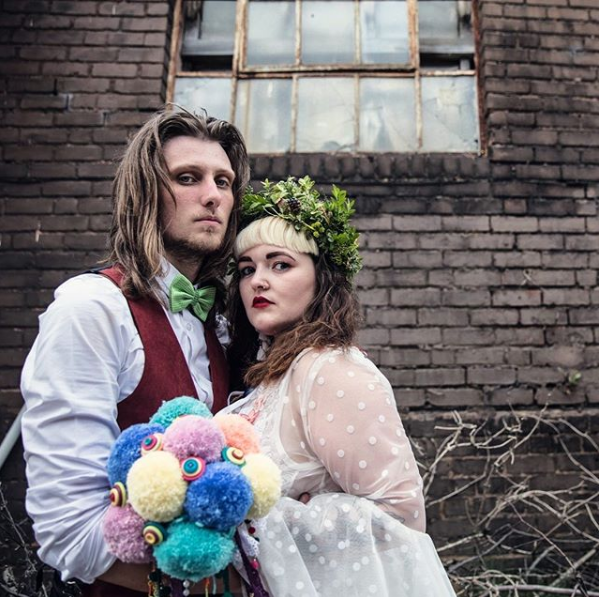 A bride and groom holding a bouquet of colorful pompoms dramatically in front of a brick wall.