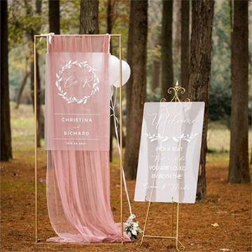 Two signs sit outside in a coniferous forest, one on a gold easel on frosted white glass with white calligraphy, and the other on clear glass with a light pink fabric drifting behind while hanging from a gold frame.