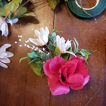 A boutonniere made of one small red rose, some greenery, two white daisies with brown middles, and some white beads.