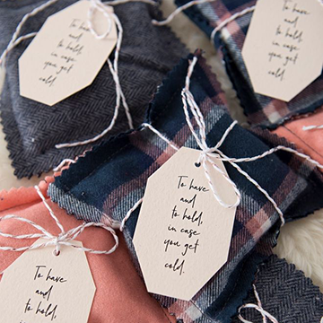 "A pile of DIY handwarmers made of blue and pink plaid cloth, each one with a small card tied to it that says, ""To have and to hold, in case you get cold"" in beautiful calligraphy."