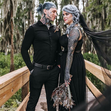 A bride with many tattoos and a gorgeous silver braid stands on a wooden bridge with her groom while holding her bouquet down at her waist. Her black veil billows out toward the camera.