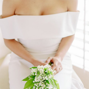A bride in a flat, off-the-shoulder wedding dress holds a bouquet of white lily of the valley in her lap while sitting in front of a white window.