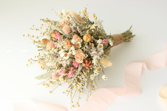 A pink and peach-colored dried wedding bouquet.
