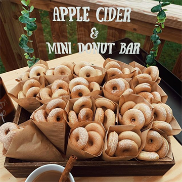 """A basket of donuts sits with a cinnamon apple cider drink with a sign that says """"Apple cider and mini donut bar""""."""