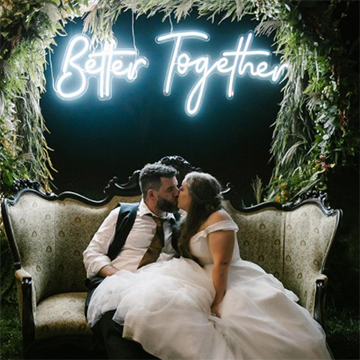 """A bride and groom kiss on a large, Victorian-style-backed couch with a light blue neon sign behind them that says """"Better Together"""" under an arch of thick greenery."""