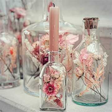 A set of 3 jars of various sizes sit on a white shelf with white and pink florals inside. One jar has a light pink candle sticking out of its neck.