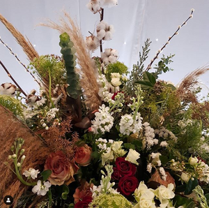 A bouquet of red roses, dried grasses, and white small blooms.