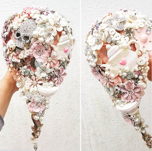A white and pink cascade bouquet made of gemstones, a skull, buttons, a teapot, and various fake flowers.