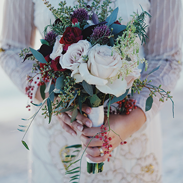 A bride holds her bouquet in front of her long-sleeved white dress. She has long fingernails and her fingers curve around the white ribbon handle of the bouquet. The bouquet holds big, white roses and a mixture of red, purple, and sage flowers and greenery while red berries hang messily on the edges of the bouquet.