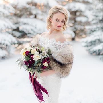 A blonde bride stands in front of snow-covered pine trees with a brown, furry shawl around her shoulders. She holds a bouquet in front of her with long, purple and pink ribbons hanging from the handle and a mixture of sage greens, white flowers, purple flowers, and gold flowers.
