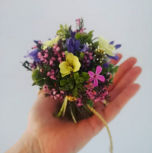 A small bouquet of pink, purple, and yellow flowers and a variety of greens is held in the palm of a person's hand in front of a white background.