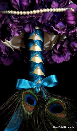 A close-up of the underside of a bouquet made of purple flowers, with a blue and white ribbon handle that has peacock feathers poking out of the butt of the handle.